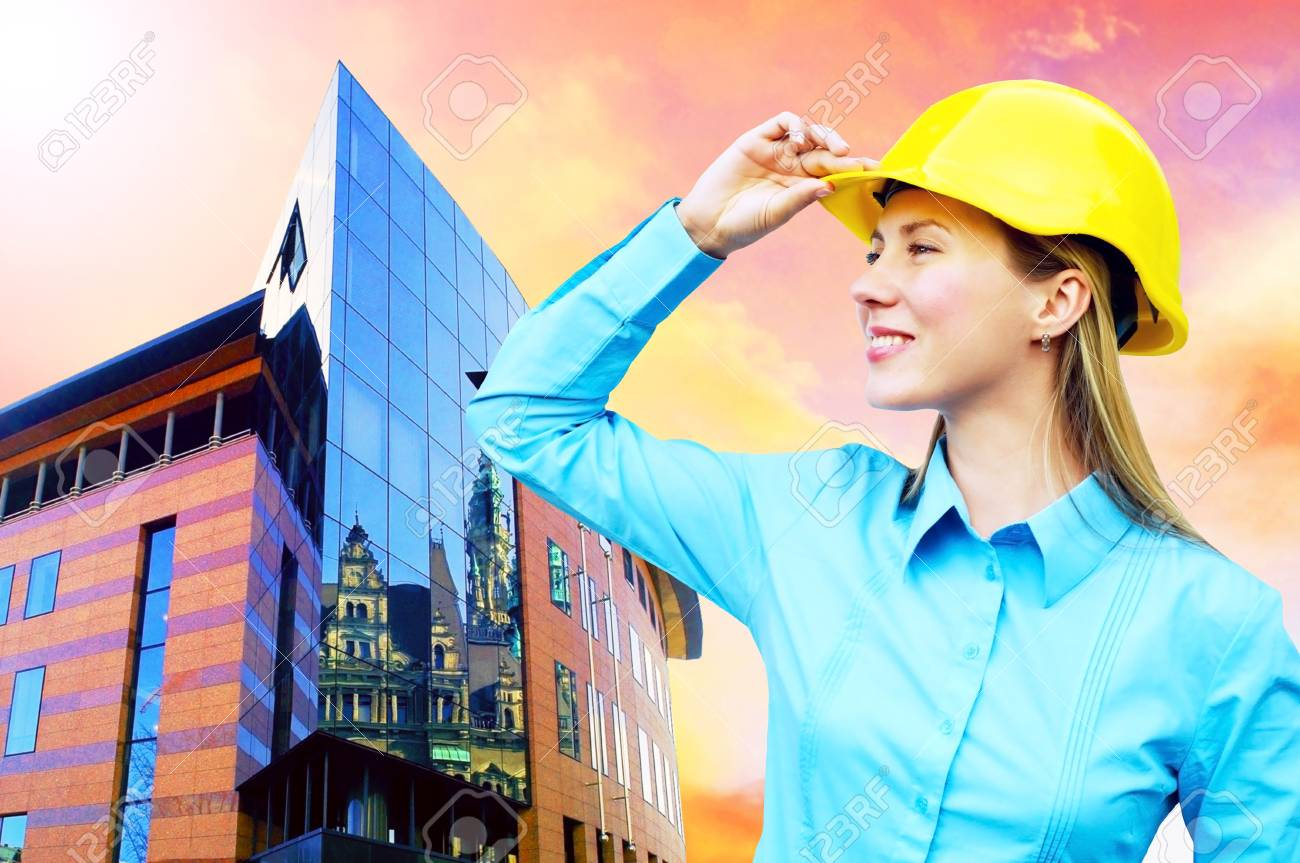 Young architect-woman wearing a protective helmet standing on the building background Stock Photo - 8255124