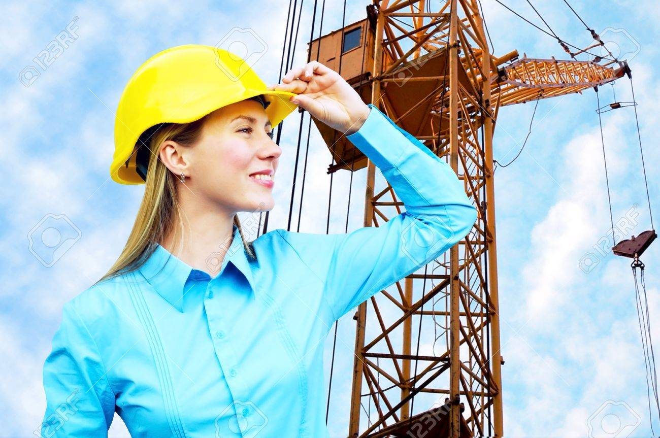 Young architect-woman wearing a protective helmet standing on the building background Stock Photo - 9788774