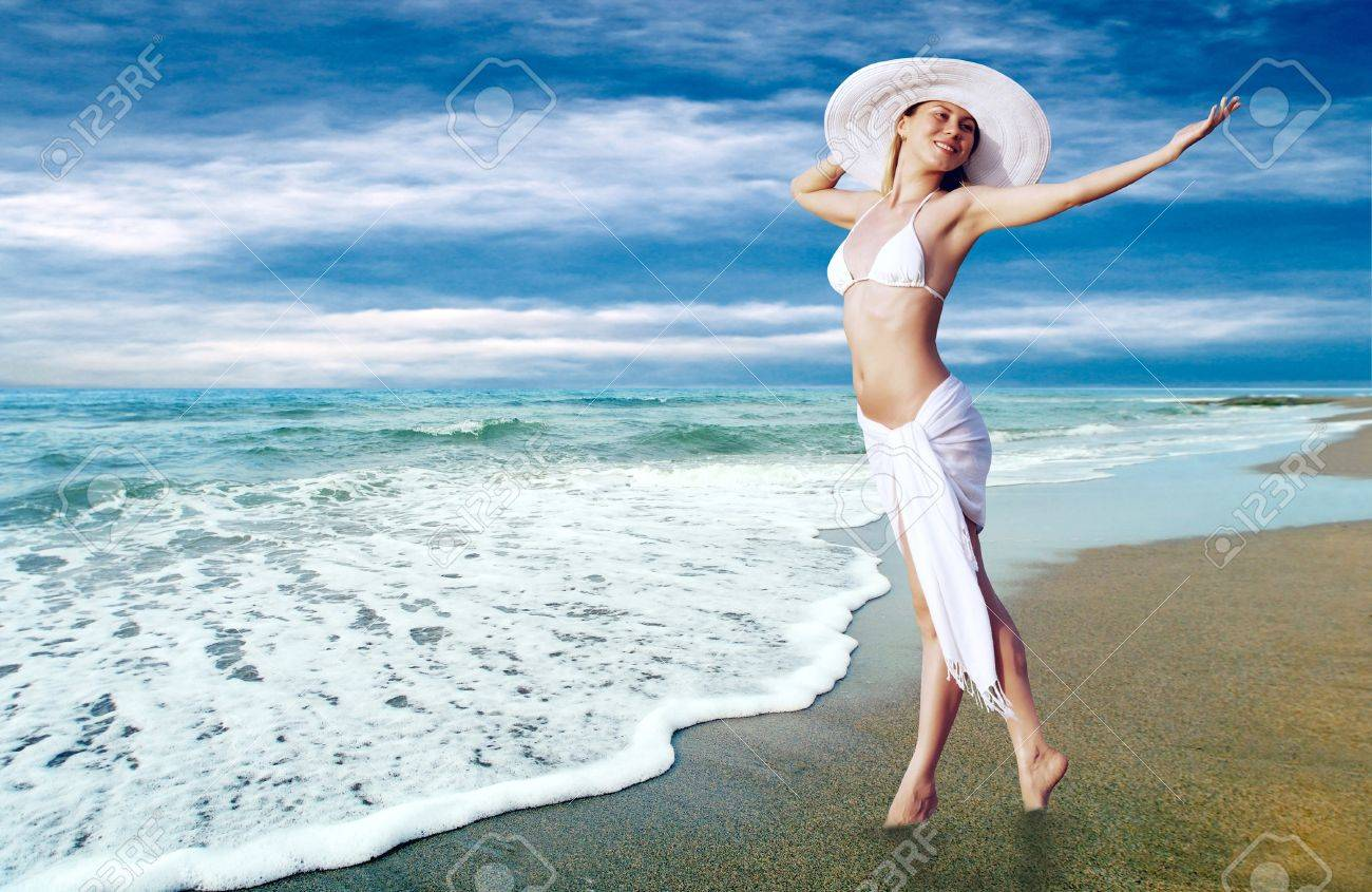 Young beautiful women in the white on the sunny tropical beach Stock Photo - 9850973