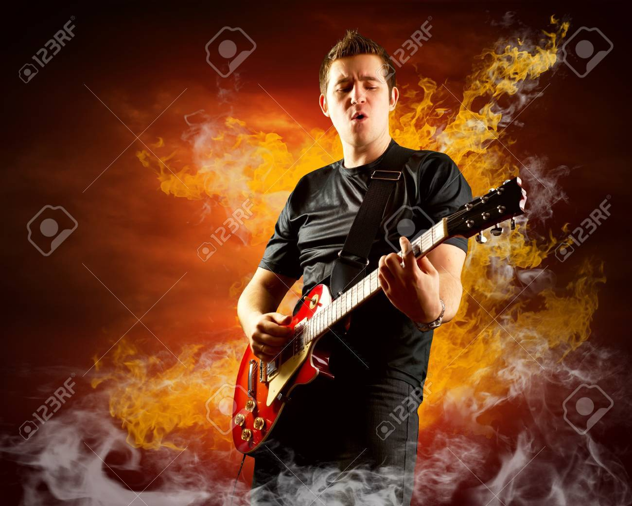 Rock guitarist play on the electric guitar around fire flames Stock Photo - 11988884
