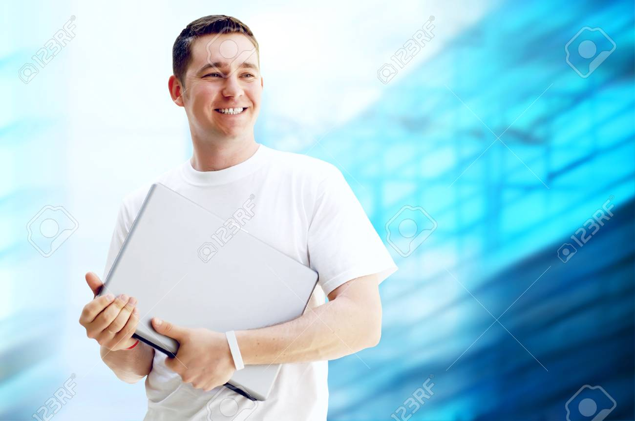 Young happy man or student with laptop and phone on the business background Stock Photo - 13650904