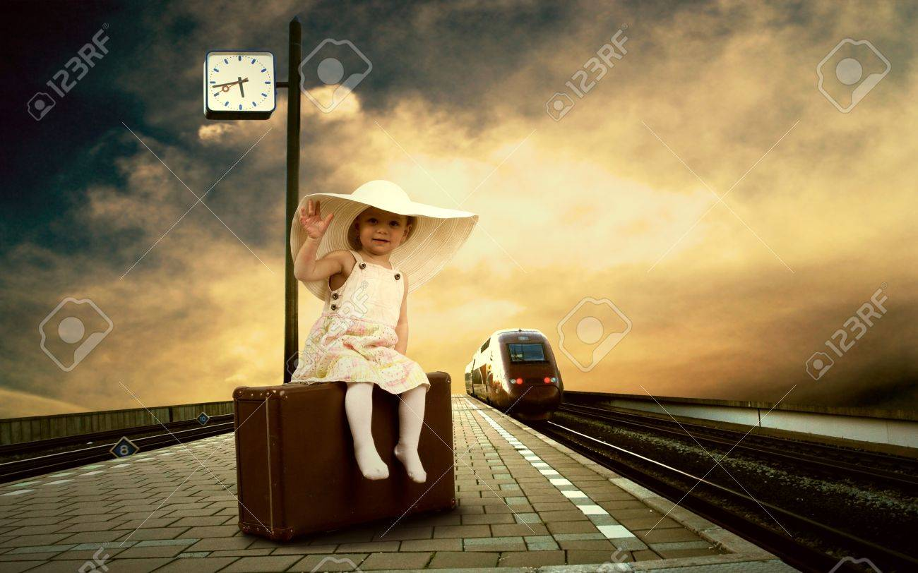Little girl sitting on vintage baggage on the train platform of railway station Stock Photo - 13658296