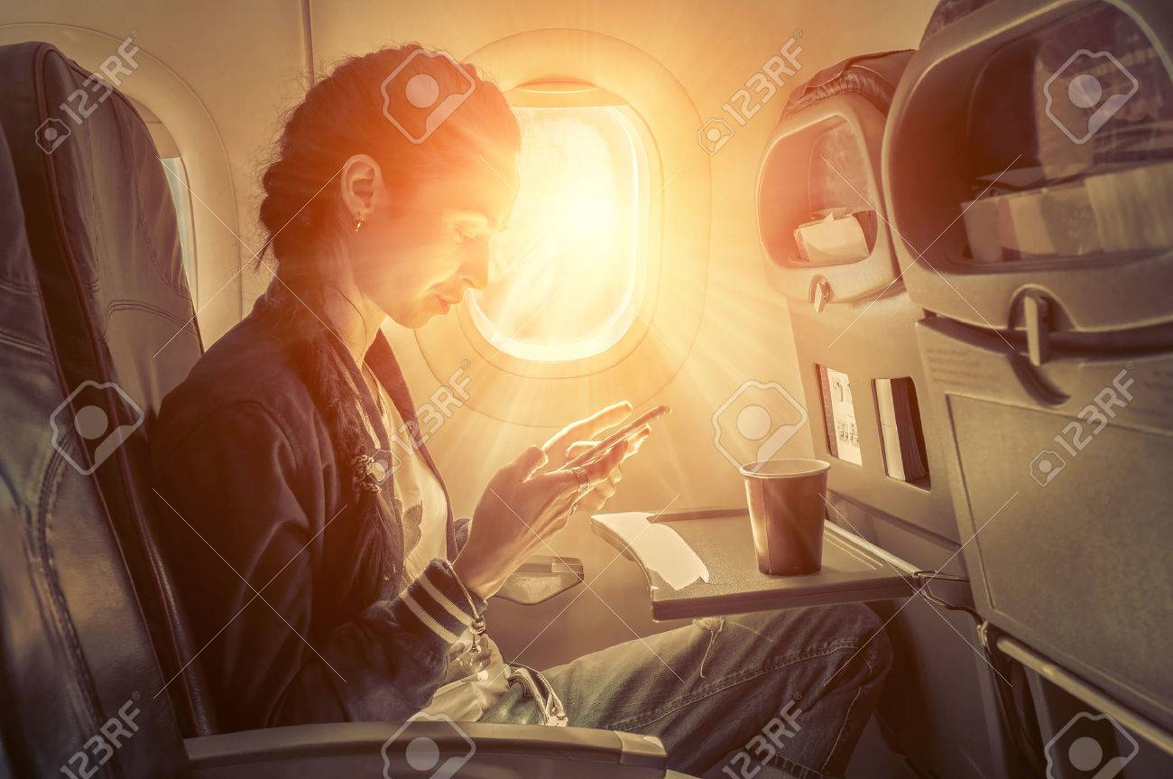 Woman sitting at airplane and looking to mobil phone. - 50687913