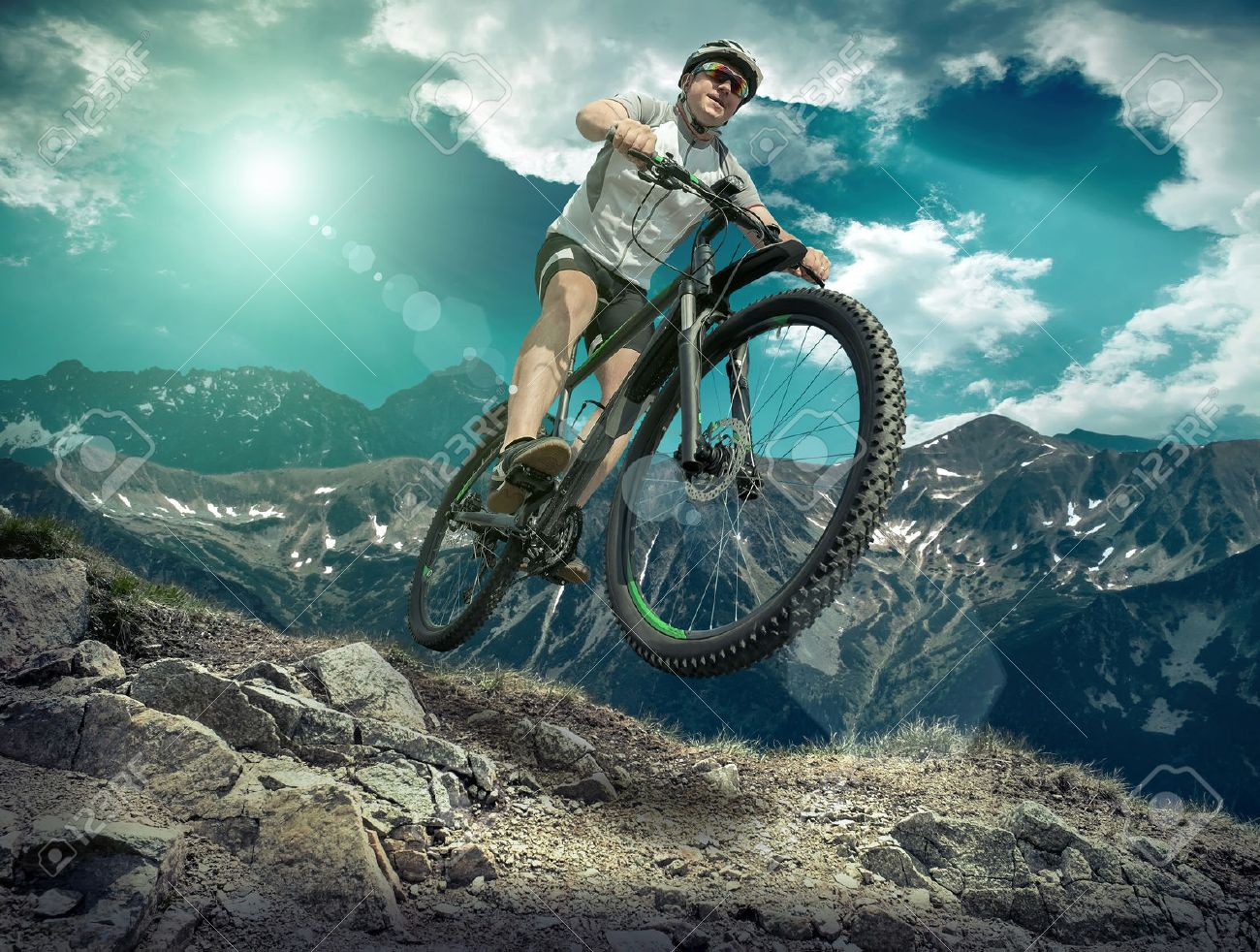Man in helmet and glasses stay on the bicycle under sky with clouds. - 50688316