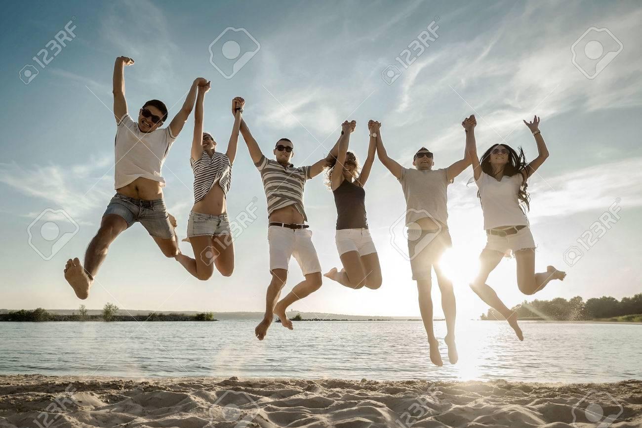Friends jumping on the beach under sunset sunlight. - 50918590