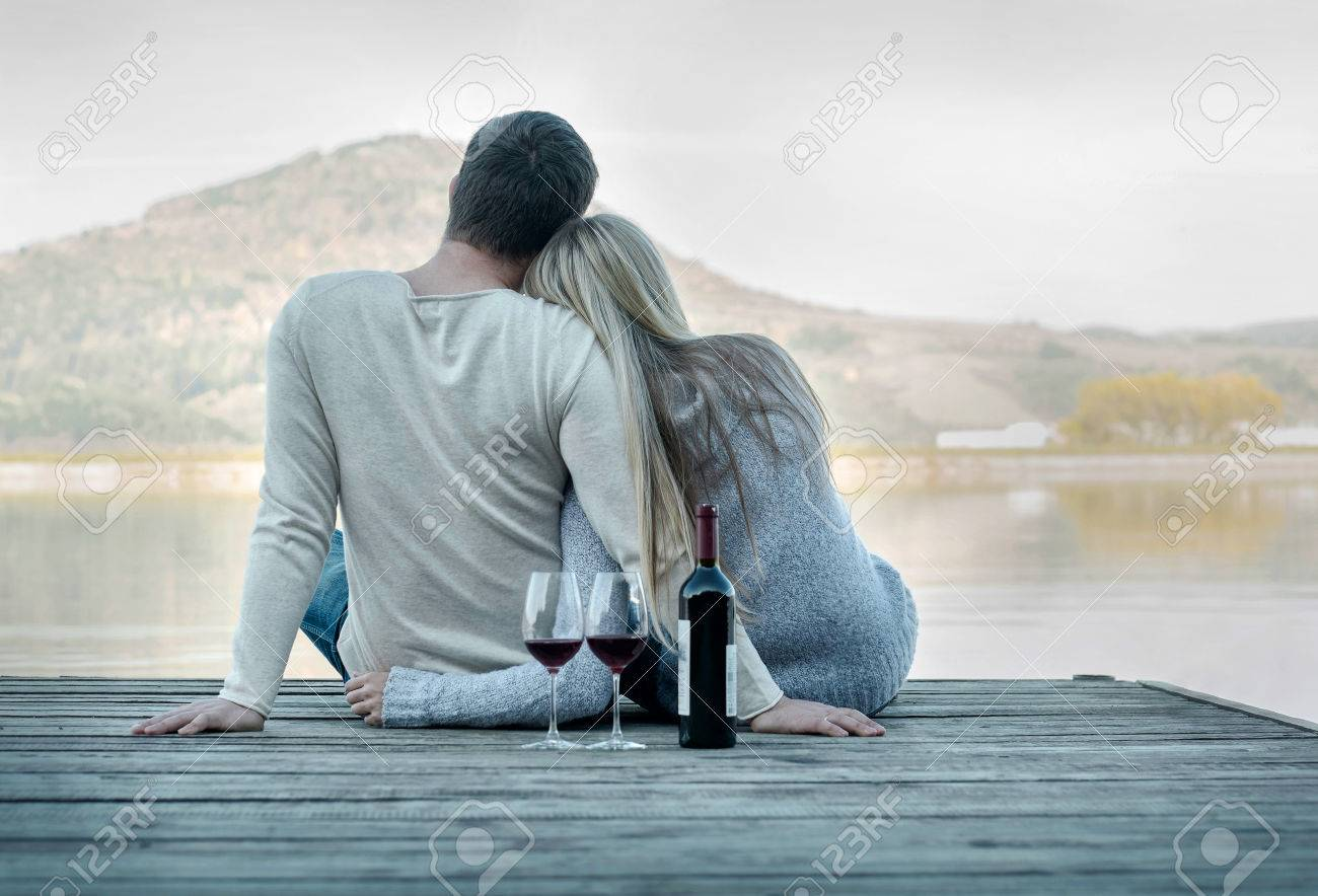 Romantic Couple sitting on the pier with red wine. - 55853210