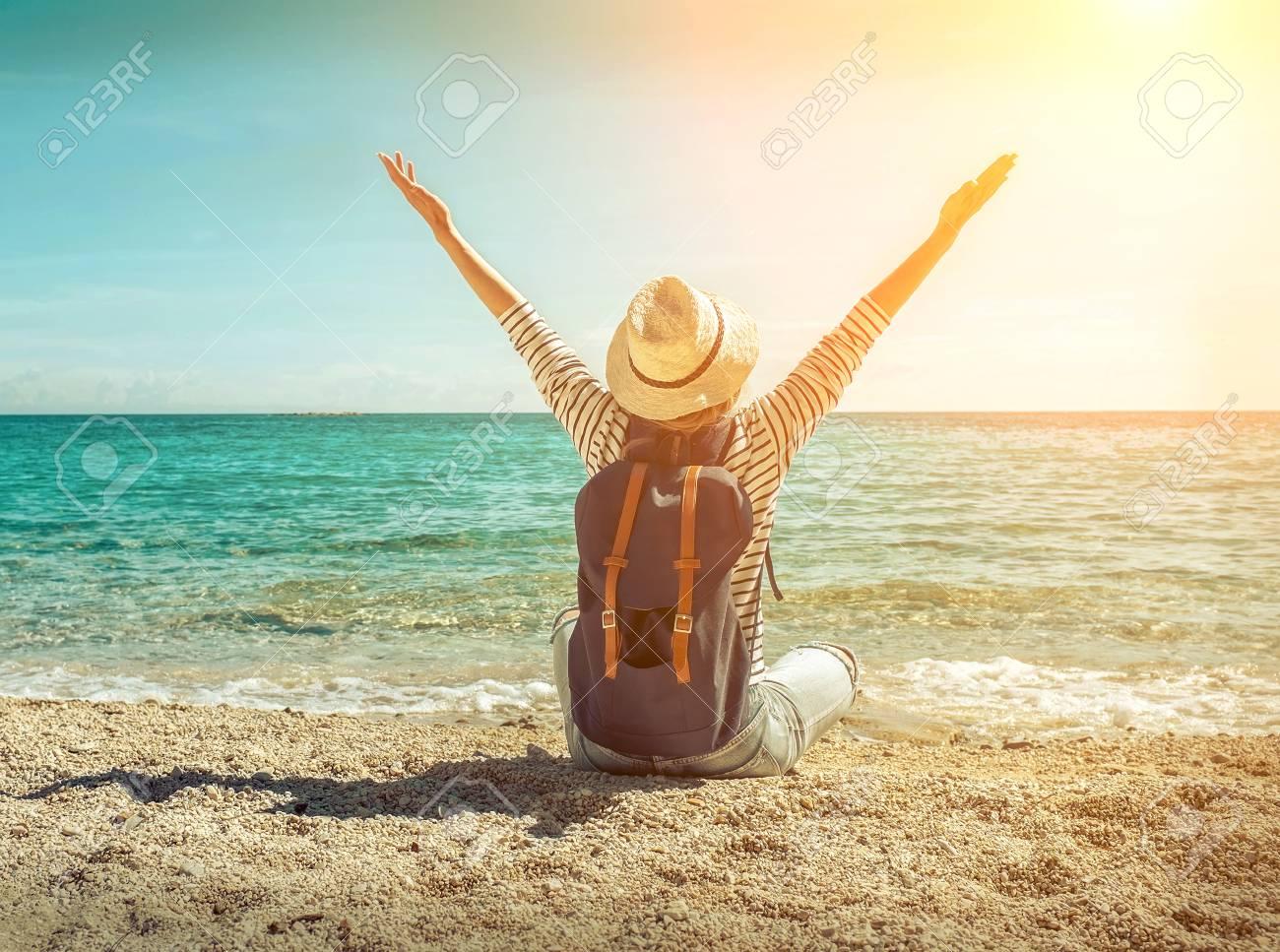 77980f2c8 Mujer Rubia En Sombrero De Verano Con Su Mochila Sentado En La Arena Por La  Playa De Mar. Vista Marítima. Libertad. Viento. Verano. Playa. Vacaciones.