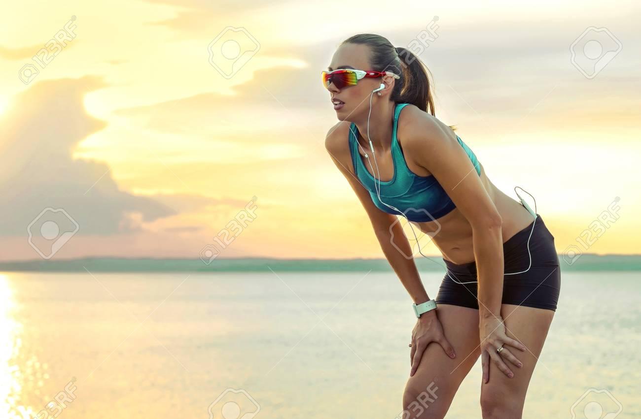 6254872613 Mujer Corriente En Gafas De Sol Deportivas. Corredor Femenino Con Su  Teléfono Inteligente Entrenamiento De Entrenamiento Al Aire Libre En La  Playa.