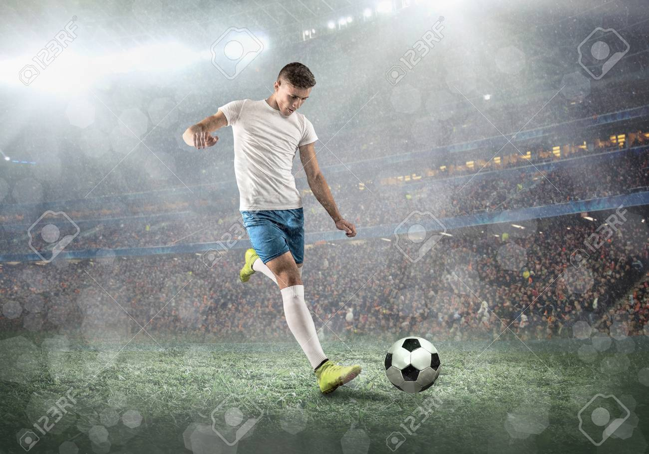 Soccer player on a football field in dynamic action at summer day under sky with clouds. Sporty man is shooting the ball outdoor. - 92627178