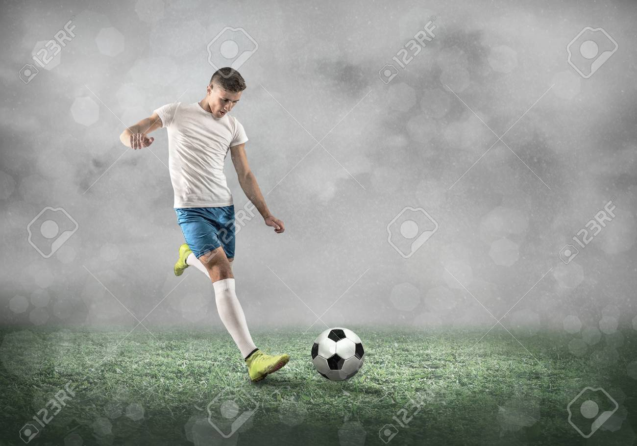 Soccer player on a football field in dynamic action at summer day under sky with clouds. Sporty man is shooting the ball outdoor. - 105288578