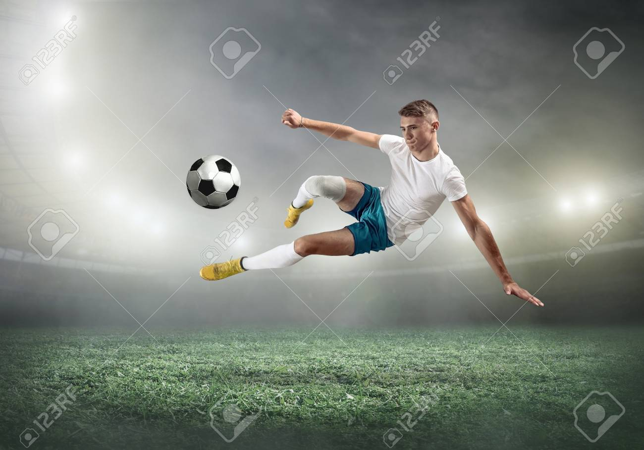 Soccer player on a football field in dynamic action at summer day under sky with clouds. Sporty man is shooting the ball outdoor. - 107721222