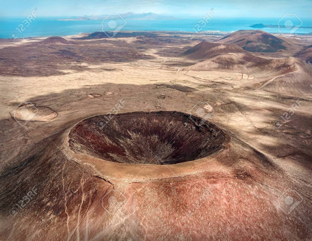 Beautiful panoramic birds eye view on Calderon Hondo, Fuerteventura island. Aerial shooting vulcano around mountains with ocean coastline at sunny day. Travell, Mountains,islands, nature, freedom concept. - 125484329