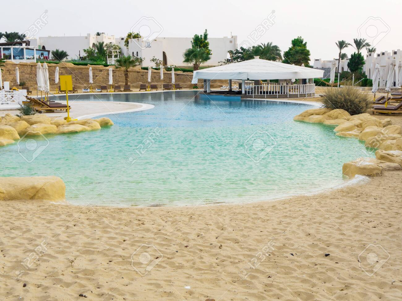 Swimming Pool With Sand Entrance In Egypt Empty Sun Loungers Stock Photo Picture And Royalty Free Image Image 118892972