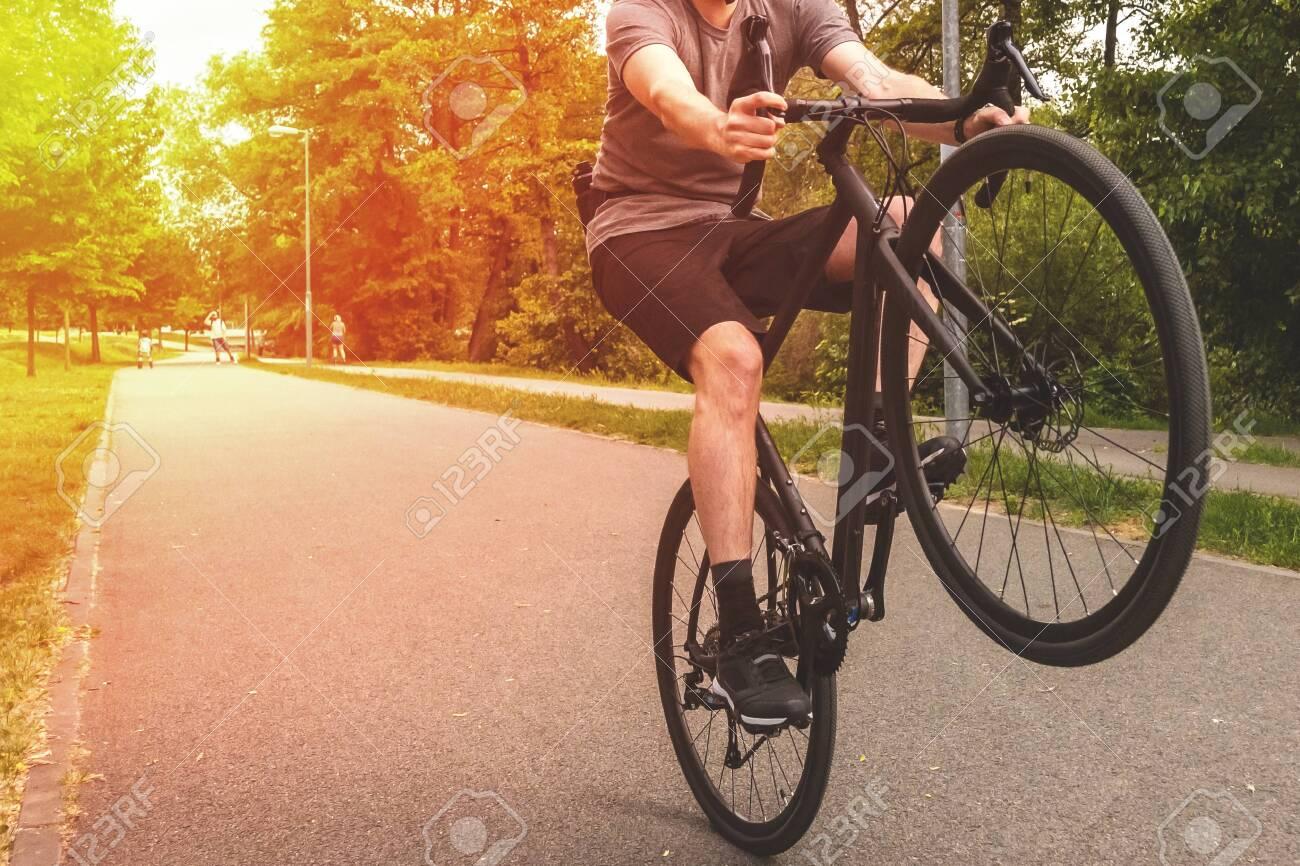 Man cycling on the path. Ride bike on back wheel. - 147814640