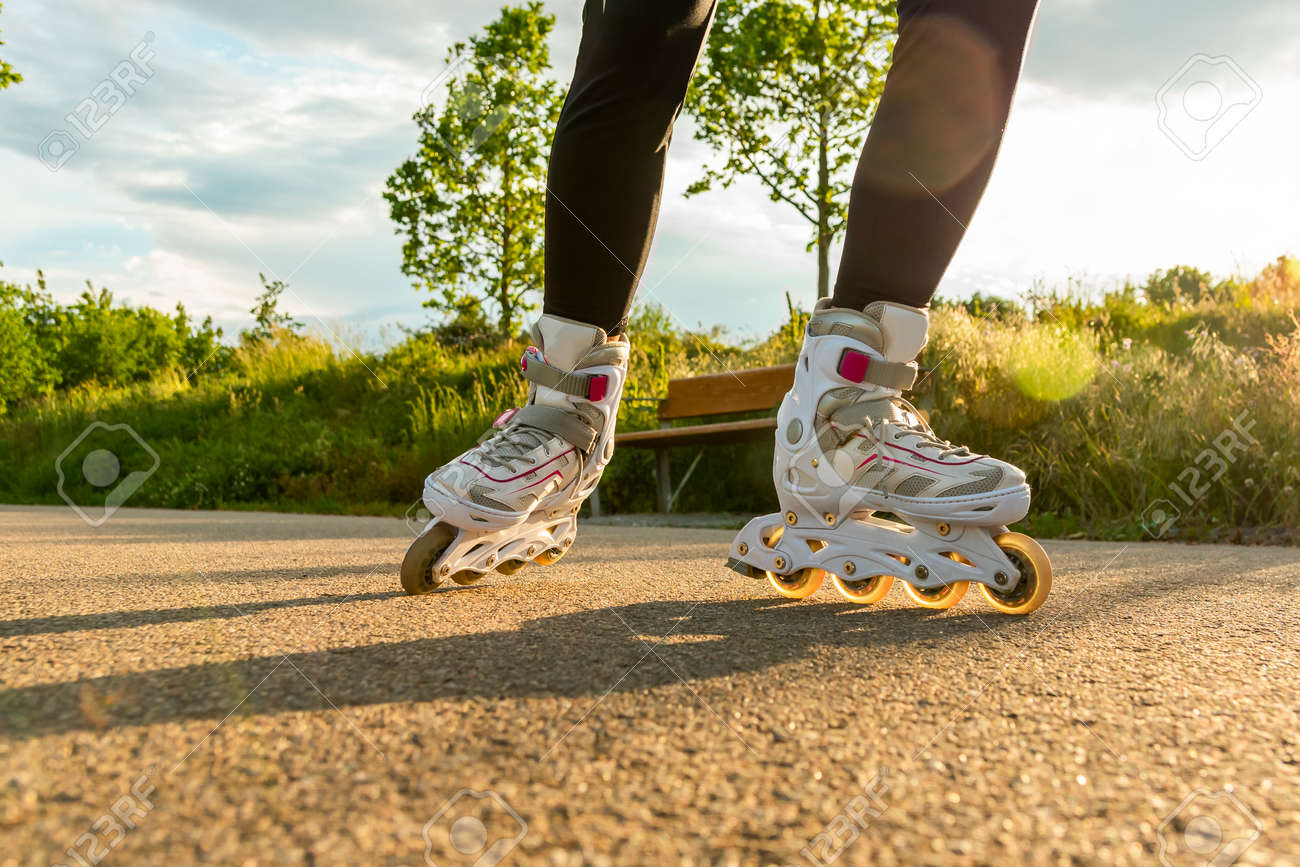 Close-up shot of white Inline skates on the path. Womans legs with roller blades at sunny day. - 150214967