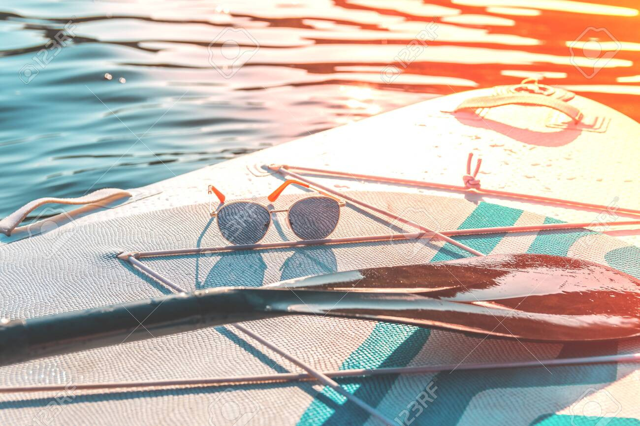 Relax and travel. Hot summer day. Water sports. Vacation at sea.Fashion sunglasses on a paddleboard surf. - 153672931