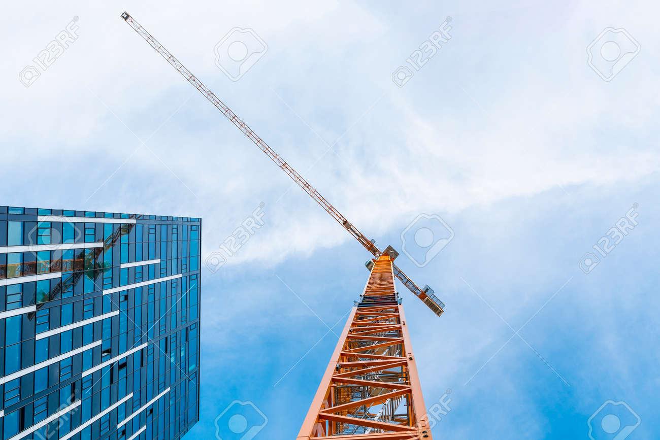 Yellow tower crane. Bottom view of a tall construction crane next to a modern building. - 155600896