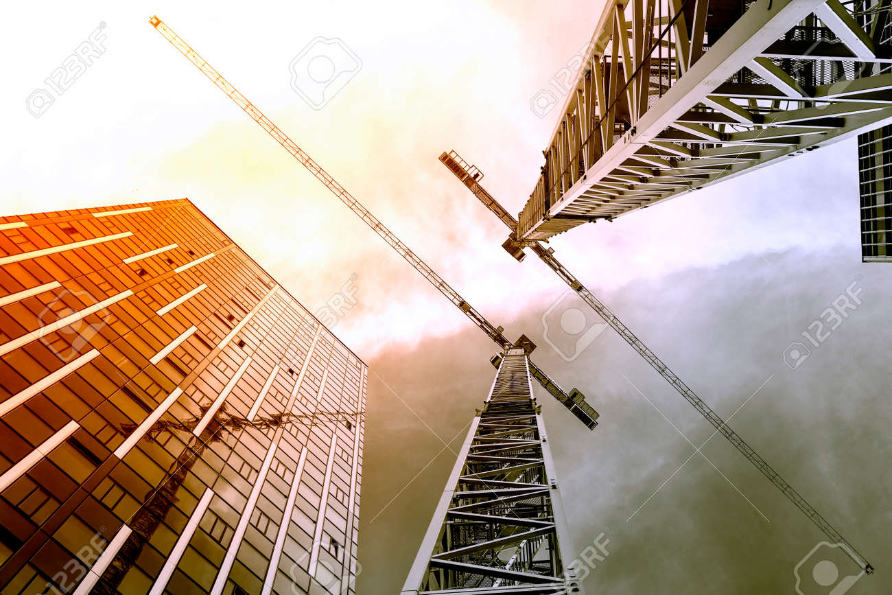 Tower crane. Bottom view of a tall construction cranes next to a modern building. Engineering and architecture design background - 155959144