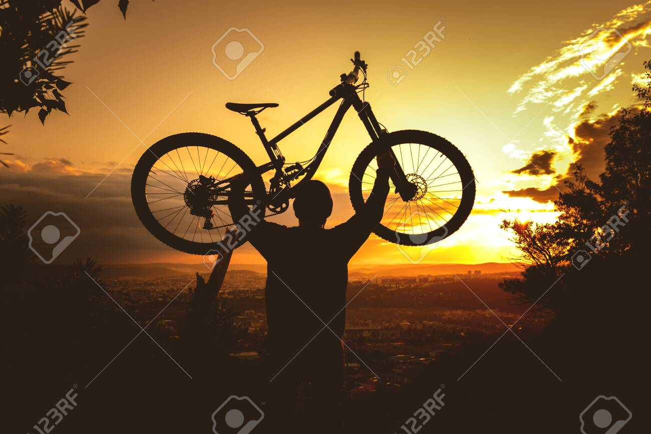 Silhouette of a mountain biker holding a bicycle over his head at sunset. MTB, enduro, freeride background. - 159556892