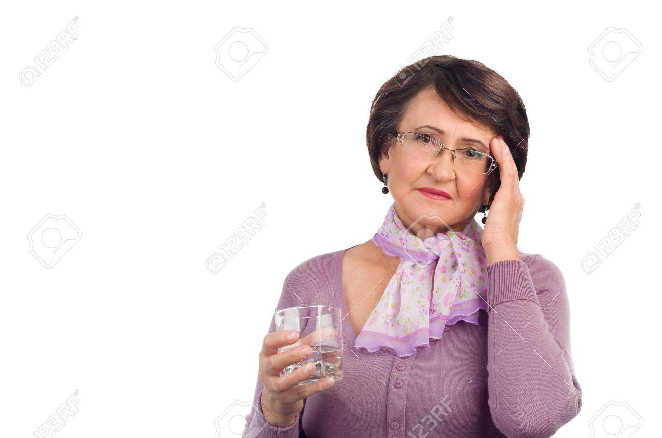 Senior woman with headache holding glass of water Stock Photo - 15042654