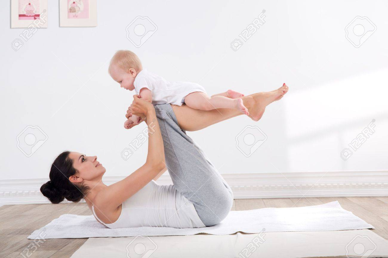 young mother does physical yoga exercises together with her baby Stock Photo - 20054409