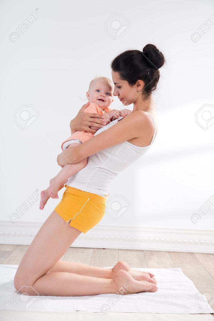 young mother does physical yoga exercises together with her baby Stock Photo - 20054412
