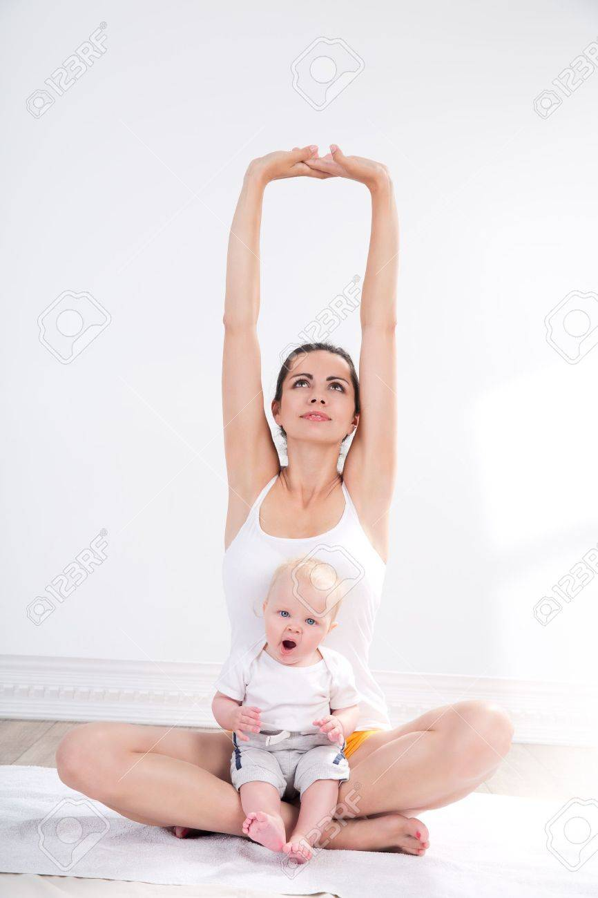 young mother does physical yoga exercises together with her baby Stock Photo - 20054404
