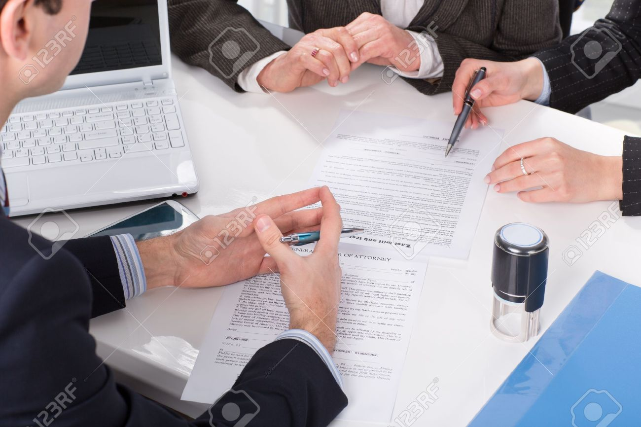 Three people sitting at a table signing documents, hands close-up Stock Photo - 20753316