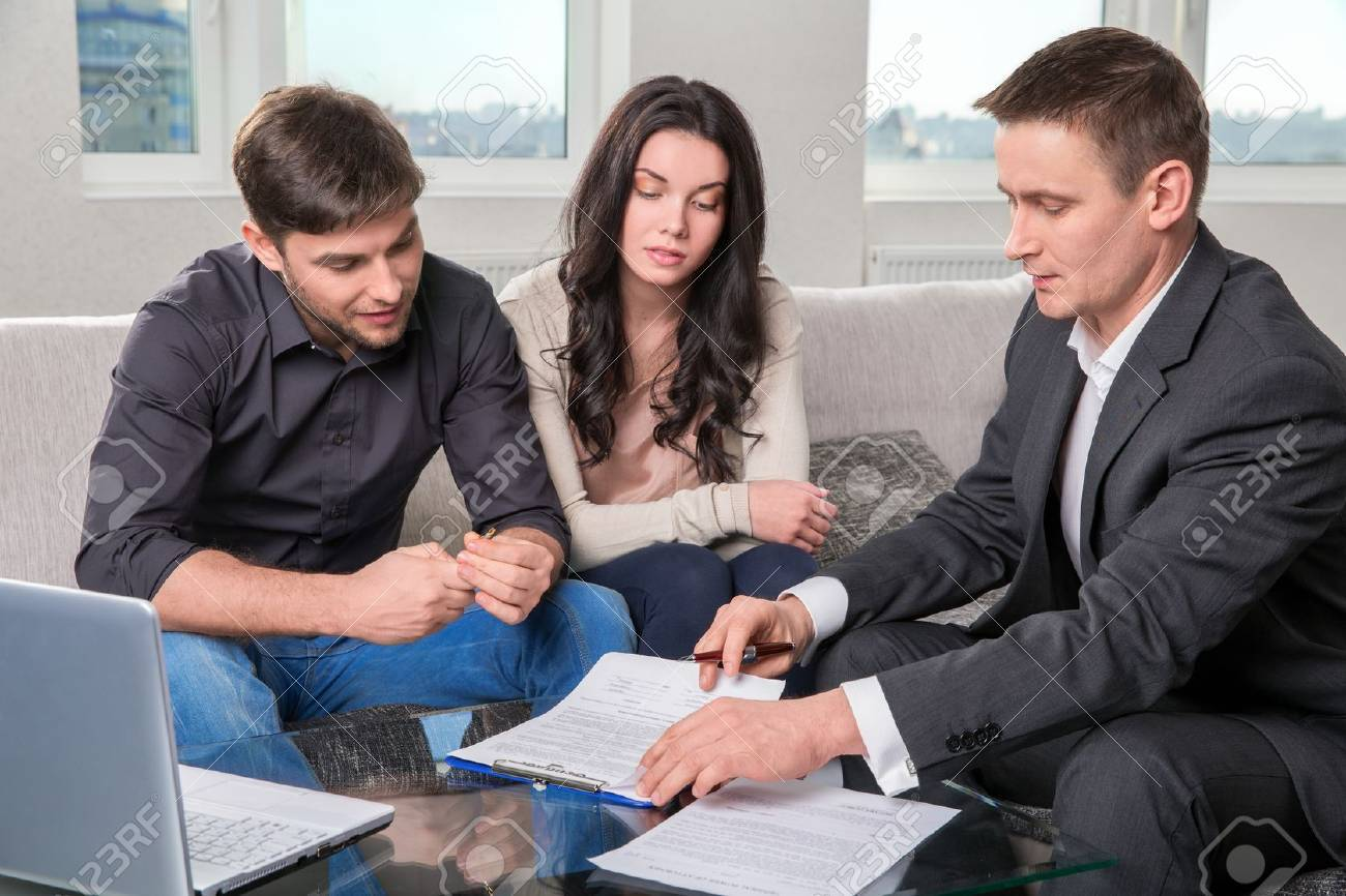 couple consults with agent, signing paperwork - 53057564