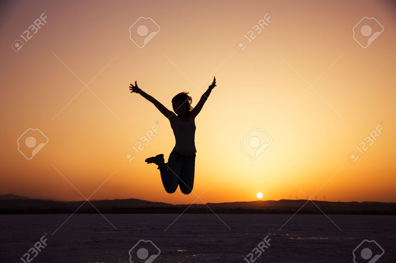 silhouette of happy woman jumping in sunset Stock Photo - 37046532