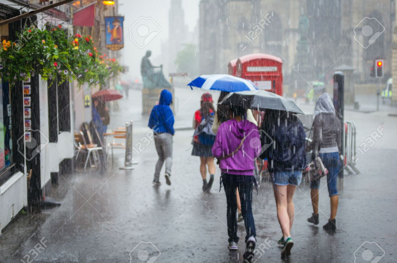 Group of girls hurry at the rain with umbrella in the city Stock Photo - 38593788