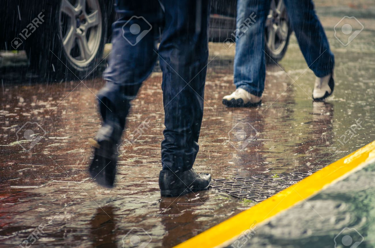 male feet stepping on wet from rain sidewalk in a city Stock Photo - 38593818
