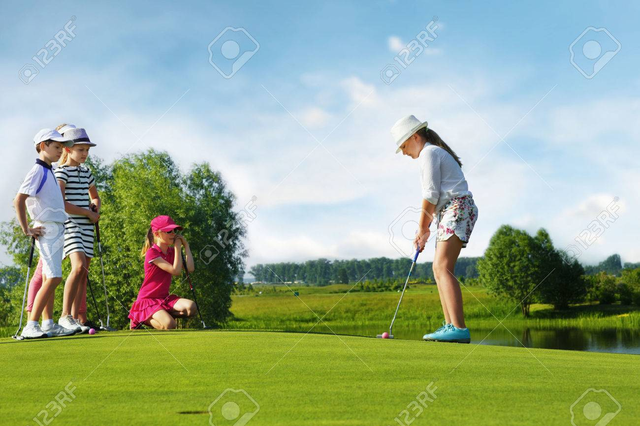Kids playing golf by putter on green Stock Photo - 47536685