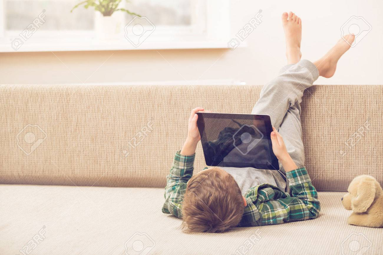 Cute little boy playing with a tablet pc on sofa at home - 53130154