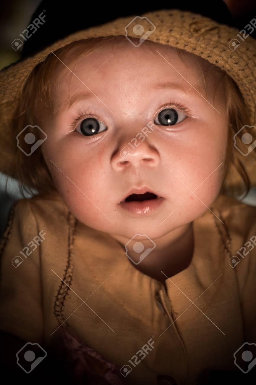かわいい赤ちゃん子供の顔に太陽の光少女の好奇心に満ちた表情子供の悲しげな表情ろうそくの光彼は慎重に見えます麦わら帽子の子幸せな子供時代