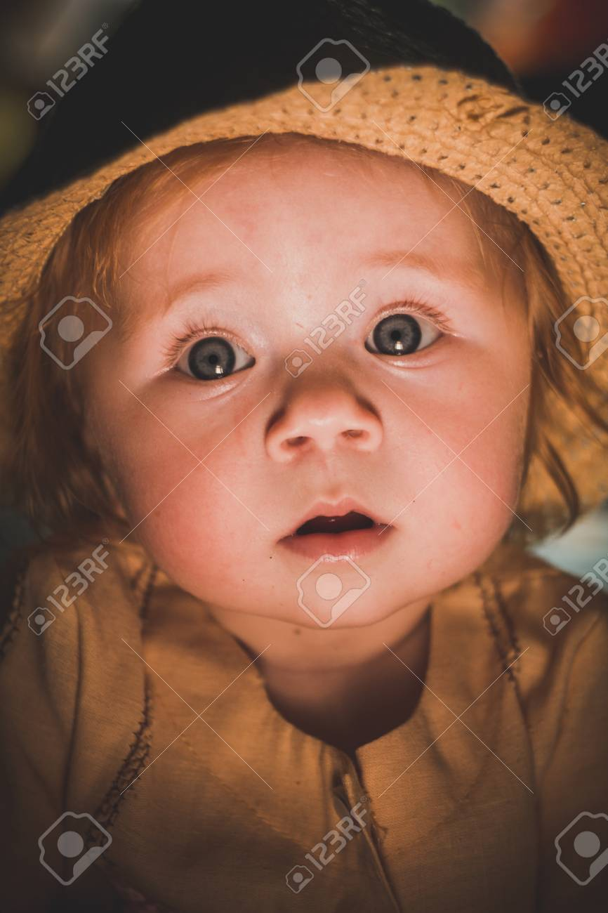 a cute baby. sunlight on the childs face. a curious look of a