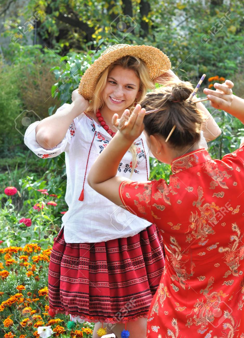 two teenage girls in traditional ukrainian and chinese clothes