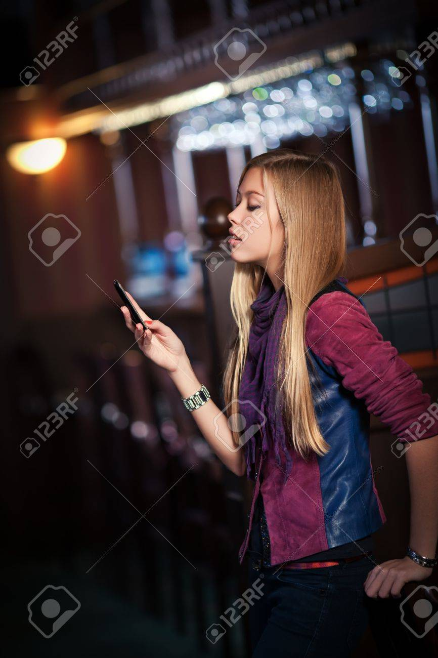 young woman sending sms on smartphone in the interior of the bar Stock Photo - 11590755
