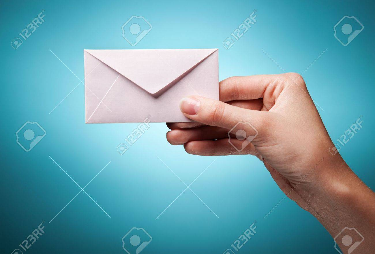 woman's hand holding closed envelope against blue background Stock Photo - 11590989