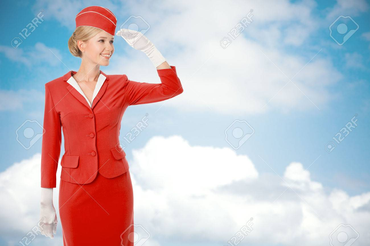 Charming Stewardess Dressed In Red Uniform. Sky With Clouds Background. - 33418732