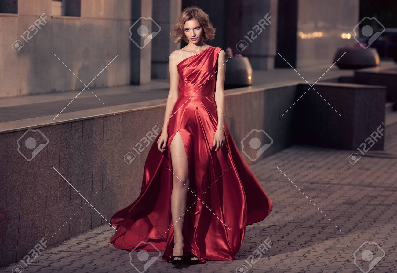 Young Beautiful Woman In Fluttering Red Dress. City Background. - 34745953