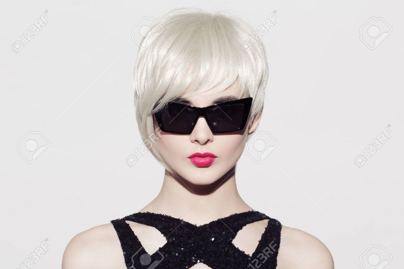 Close-up portrait of beautiful model with perfect glossy blond hair and sunglasses. White background. Space for text. - 64765776