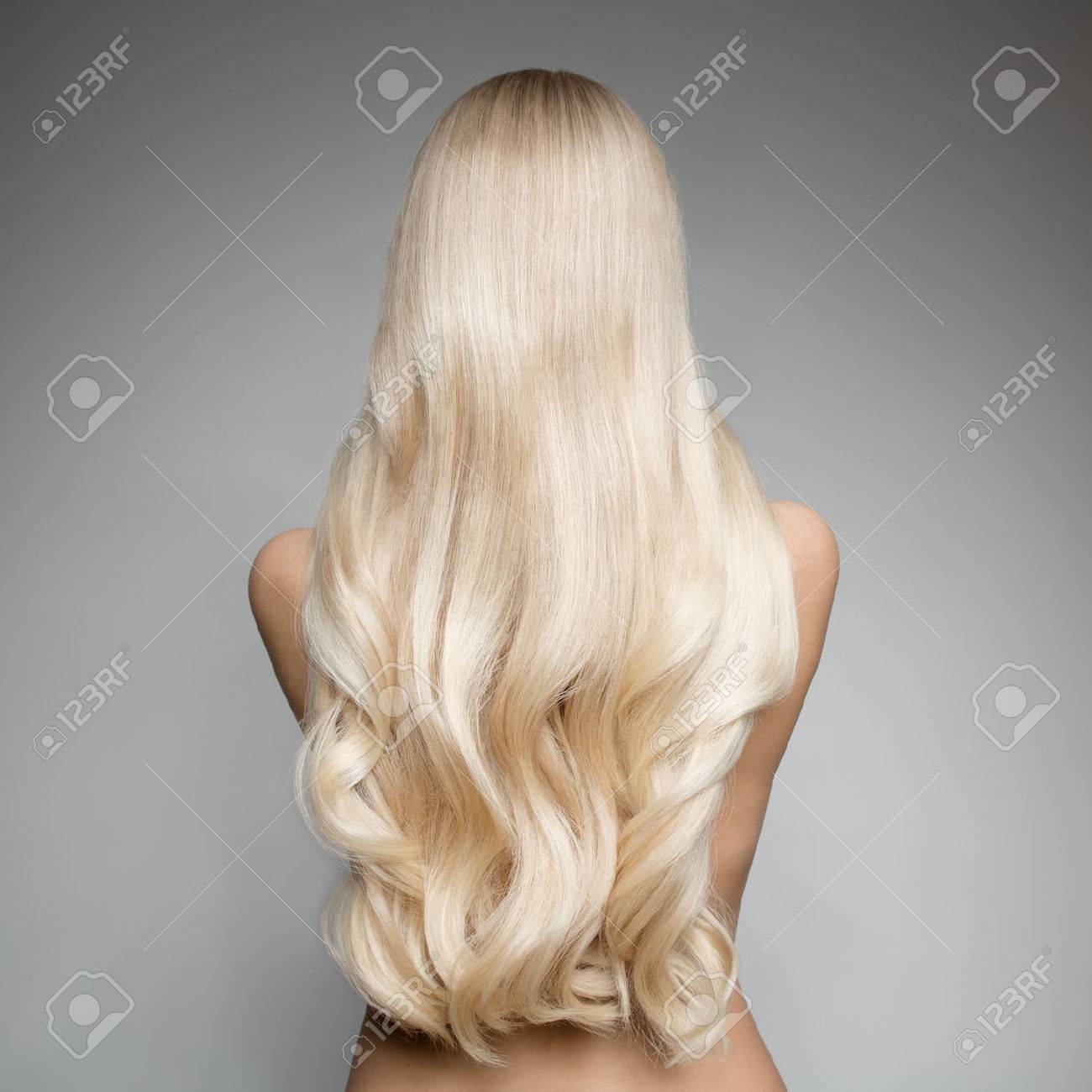 Portrait Of Beautiful Young Blond Woman With Long Wavy Hair. Back view - 66526637