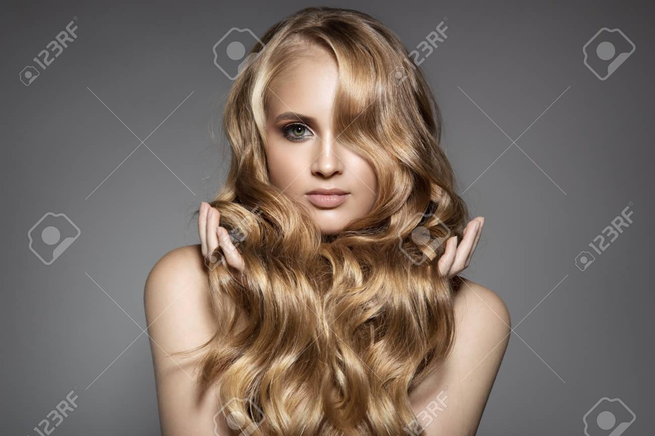 Portrait Of A Beautiful Young Blond Woman With Long Wavy Hair - 75170331