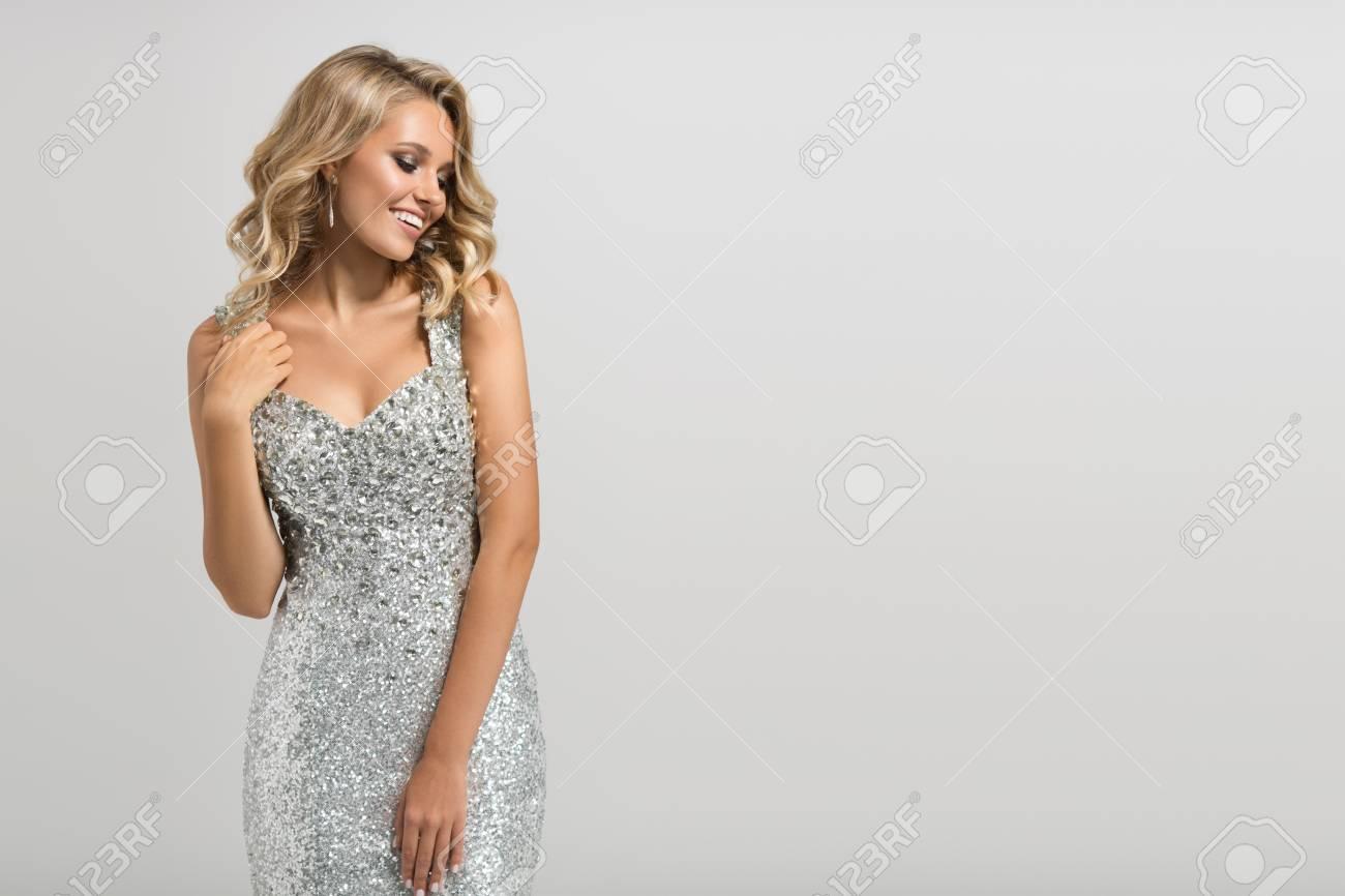 Beautiful woman in shining silver dress on gray background. - 88777017
