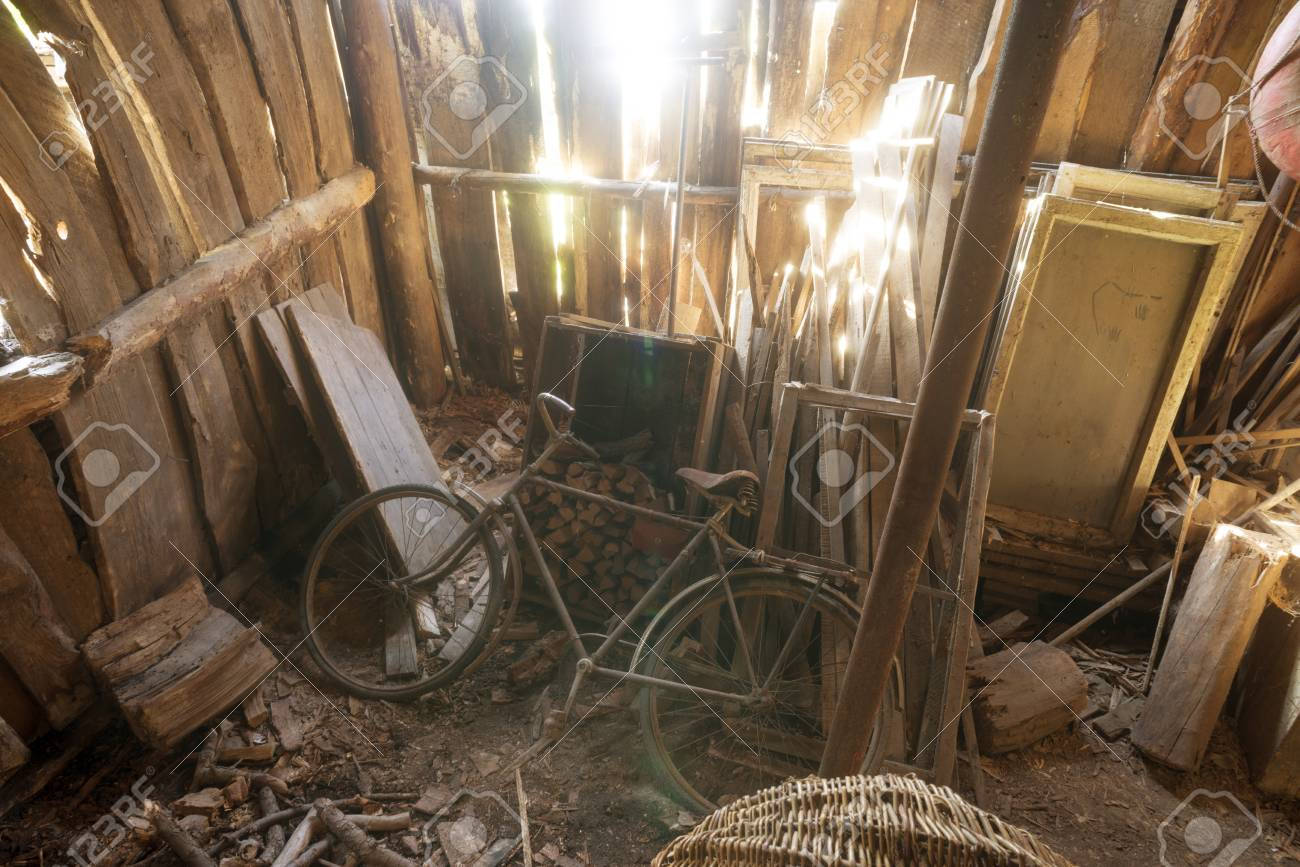 Old Wooden Abandoned Barn Interior With Bright Sun Beams Fallen Through Cracks In The Wall Stock