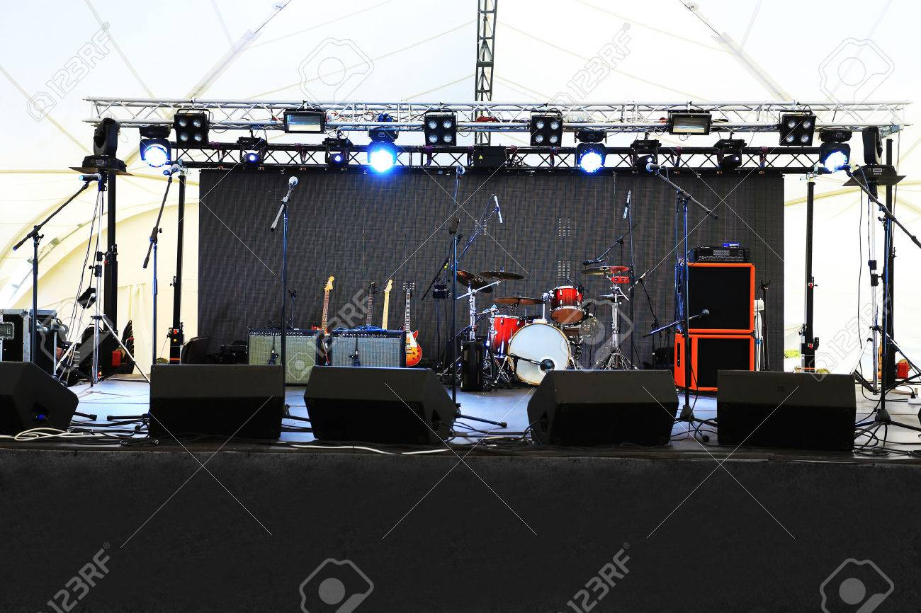 Empty outdoor rock stage - Outdoor Concert Stage An Empty Stage Before The Concert With Floodlight And Musical Instruments Stock