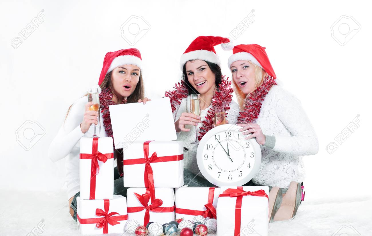Three Young Women In Hats Of Santa Claus With Christmas Gifts ...