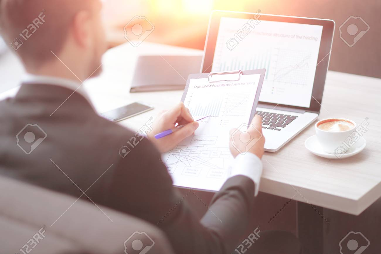closeup.businessman checking financial documents sitting at the Desk in the office. - 123535778