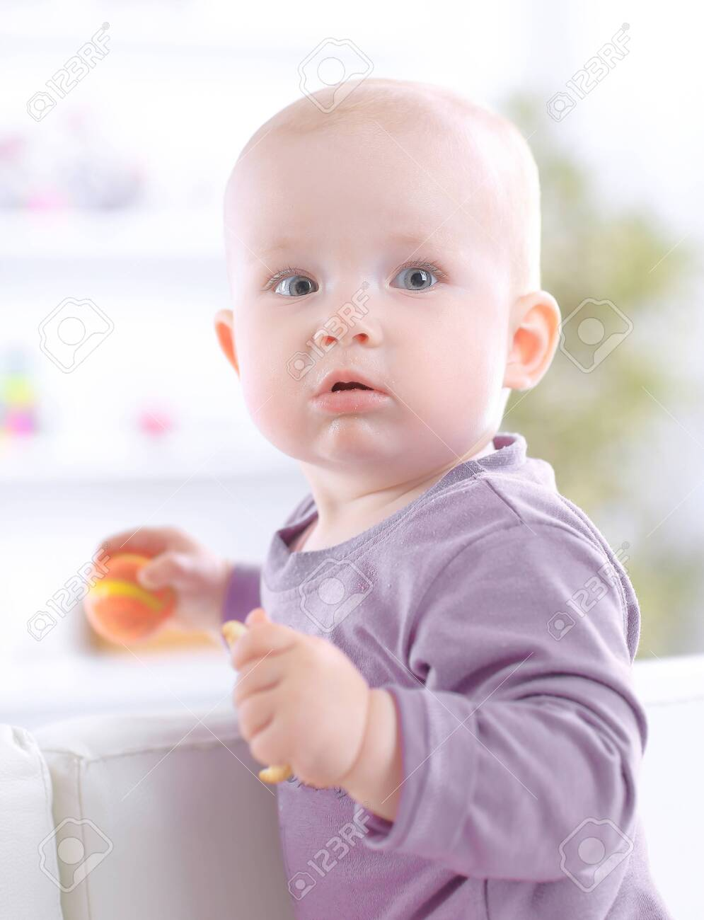 close up.cute baby eating a cookie while sitting on the couch - 123600968